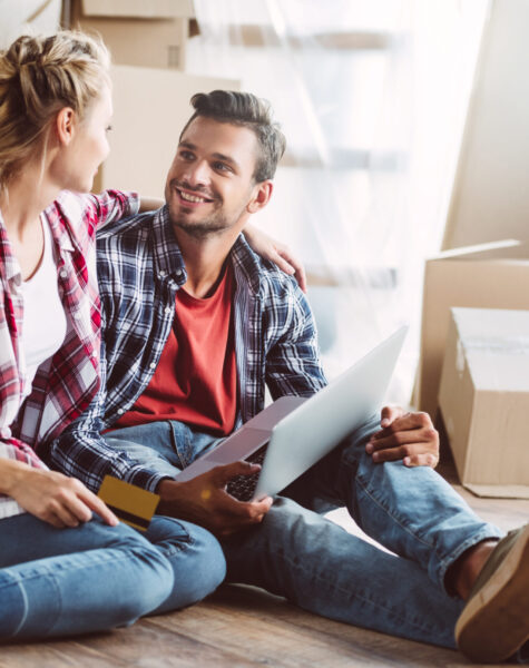 happy young couple with laptop and credit card smiling each other in new house