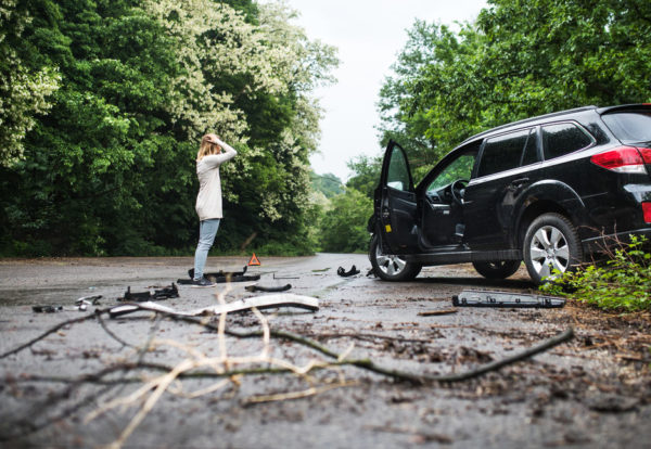 young-woman-standing-by-the-damaged-car-after-a-ca-SHE6YK7_Easy-Resize.com_-1