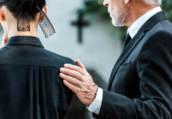 cropped-view-of-man-touching-woman-on-funeral-WXHCDM2_Easy-Resize.com