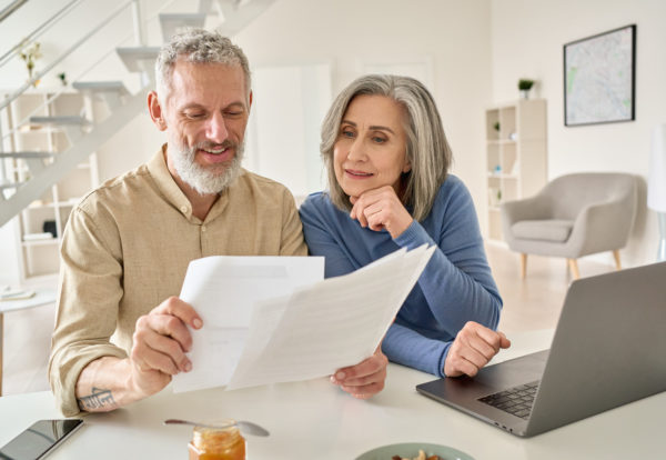 middle-aged-couple-reading-paper-bills-calculating-65JMF9Q_Easy-Resize.com