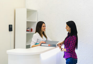 receptionist-at-medical-clinic-with-patient-JD2M64X_Easy-Resize.com